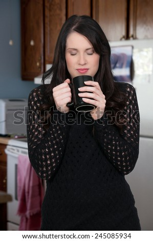 Beautiful young woman drinking and smelling coffee - stock photo