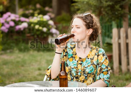 Beautiful young woman drinking beer in a terrace outdoors