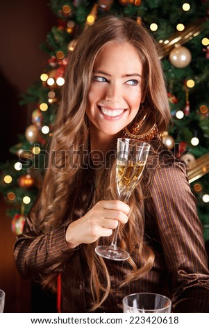 Beautiful young woman drinking champagne - stock photo