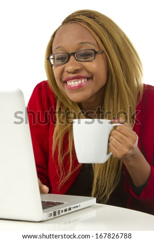 Beautiful young woman drinking coffee and working on her laptop looking happy