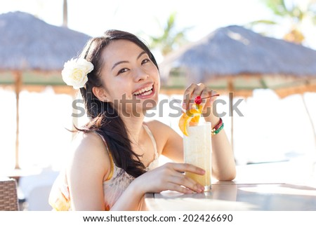 beautiful young woman drinking fruit juice on tropical island beach
