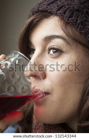 Beautiful young woman drinking glass of cranberry juice - stock photo