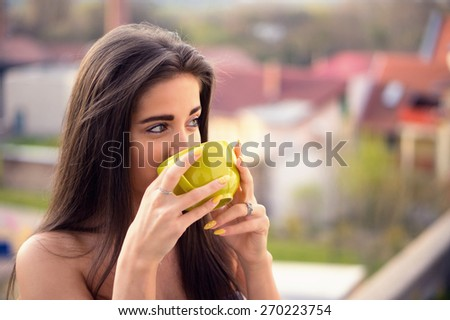Beautiful young woman drinking her steaming coffee in front of the window and watching the city / Color effects, a soft film noise and a custom white balance is added to reach the Vintage look