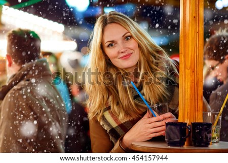 Beautiful young woman drinking hot punch, mulled wine on German Christmas market. Happy girl in winter clothes with lights on background. Family, tradition, holiday concept