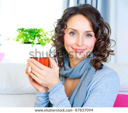 Beautiful Young Woman drinking hot tea - stock photo