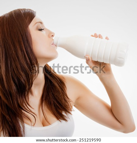 Beautiful young woman drinking milk - stock photo
