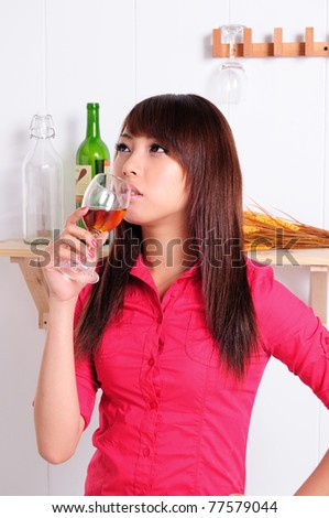 Beautiful young woman drinking red wine with the right hand
