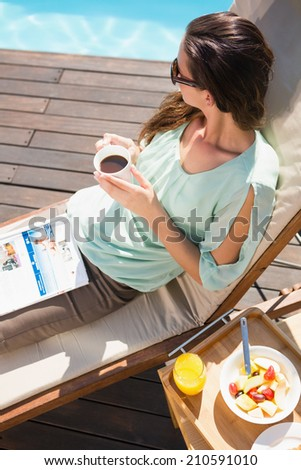 Beautiful young woman drinking tea by swimming pool with breakfast on table - stock photo