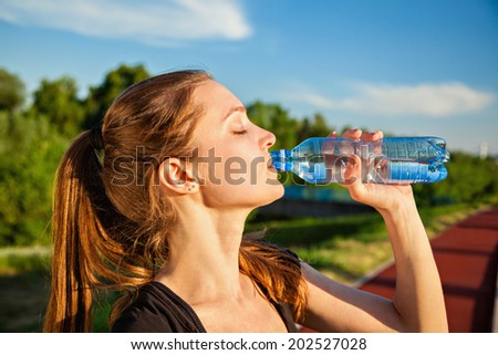 Beautiful Young Woman Drinking Water After Training - stock photo