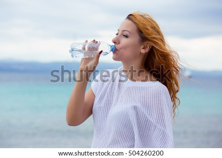 beautiful young woman drinking water in summer beach outdoor with sea background