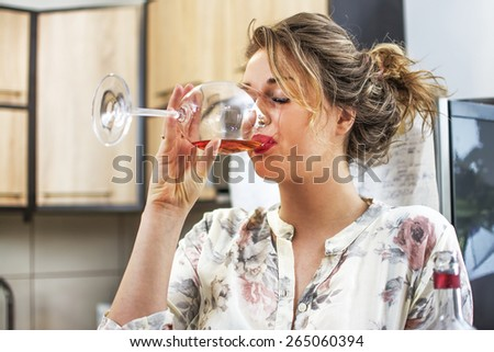 Beautiful young woman drinking wine and keeping eyes closed. - stock photo