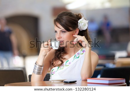 Beautiful young woman drinks coffee at cafe - stock photo