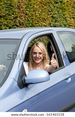 Beautiful young woman driver giving a thumbs up of appreciation and success as she tries out her new car