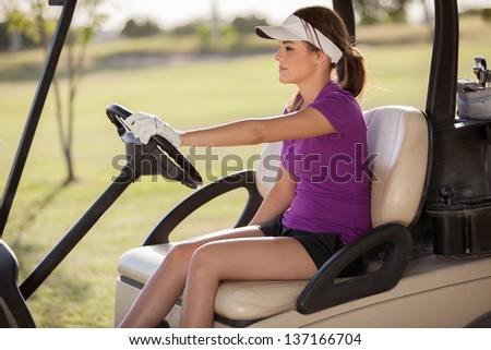Beautiful young woman driving a golf cart on a sunny day