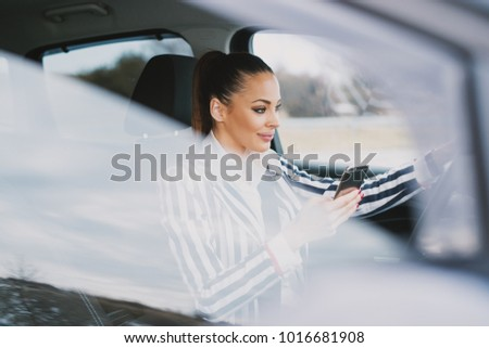 Beautiful young woman driving and texting in the city.