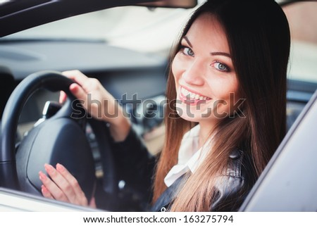 Beautiful young woman driving the car - stock photo