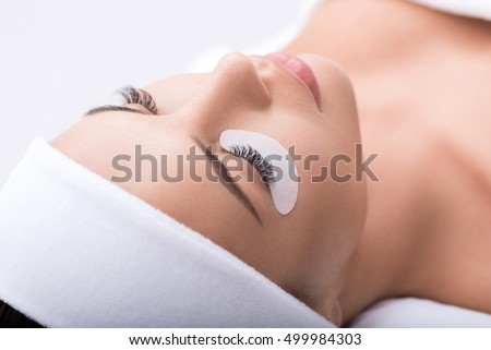 Beautiful young woman during eyelash extension