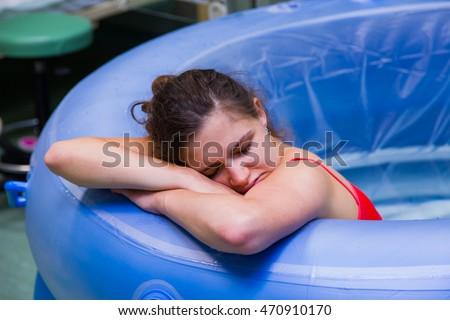 Beautiful young woman during labour, having painful cramps, giving birth in water.
