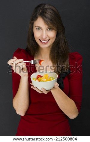 Beautiful young woman eating a fruit salad, over a black background - stock photo