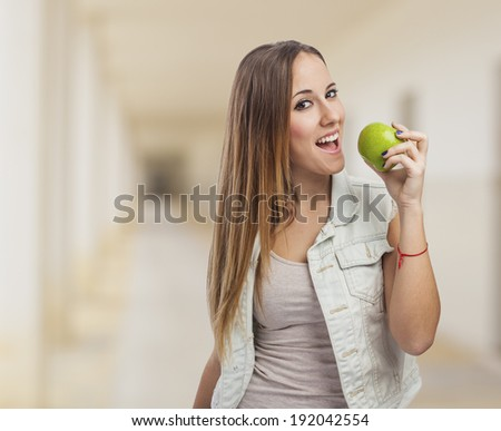 beautiful young woman eating a green apple - stock photo
