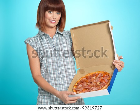 beautiful young woman, eating a pizza pie from the delivery box, smiling, on blue background
