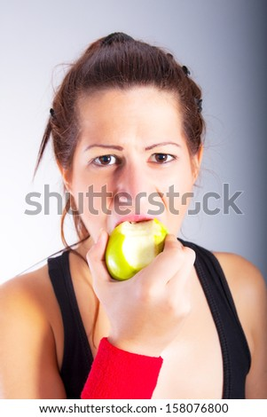 beautiful young woman eating an apple - stock photo