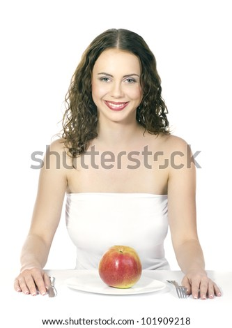 Beautiful young woman eating an apple at table on white background - stock photo