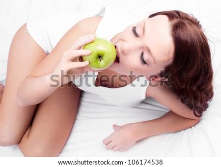 beautiful young woman eating an apple in bed at home, top view - stock photo