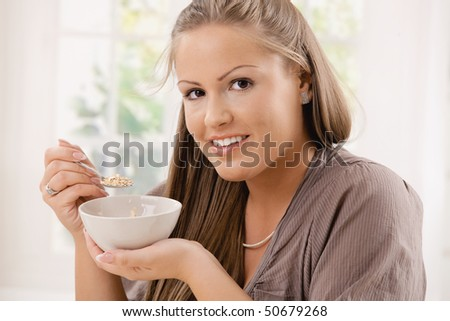 Beautiful young woman eating breakfast cereal. Selective focus on face. - stock photo