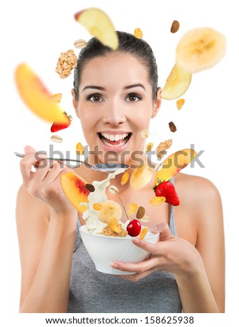 Beautiful young woman eating cereals and fruit - stock photo