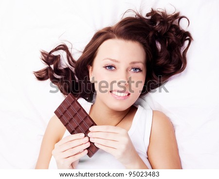 beautiful young  woman eating chocolate in bed at home - stock photo