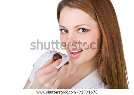 Beautiful young woman eating chocolates, isolated on white background - stock photo