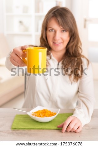 Beautiful young woman eating cornflakes and holding cup of coffee at home - stock photo