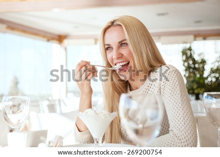 Beautiful young woman eating ice-cream in cafe - stock photo