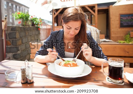 Beautiful young woman eating lasagne in restaurant - stock photo
