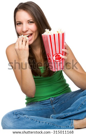 Beautiful young woman eating popcorn - stock photo