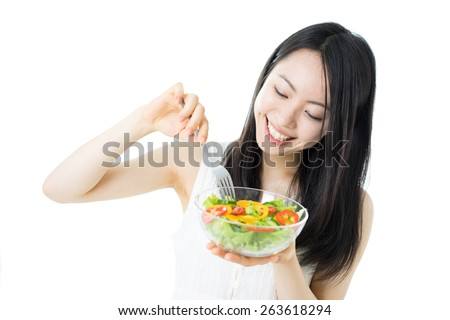 beautiful young woman eating salad, isolated on white background - stock photo
