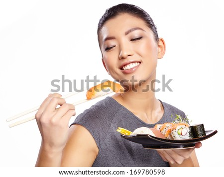 Beautiful young woman eating sushi. Isolated on white. - stock photo