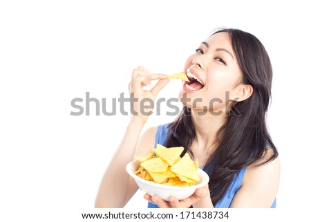Beautiful young woman eating tortilla chip