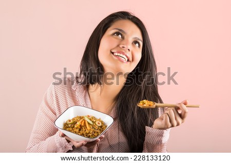 beautiful young woman eating yellow rice smiling looking up - stock photo