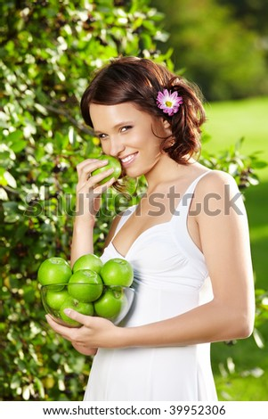 Beautiful young woman eats an apple in a summer garden - stock photo