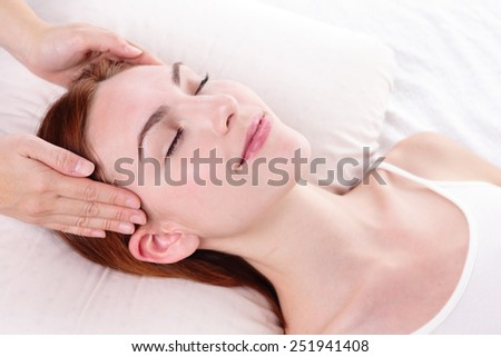 Beautiful young woman enjoy face massage at spa, caucasian beauty - stock photo