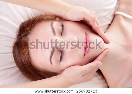 Beautiful young woman enjoy face massage at spa, caucasian beauty