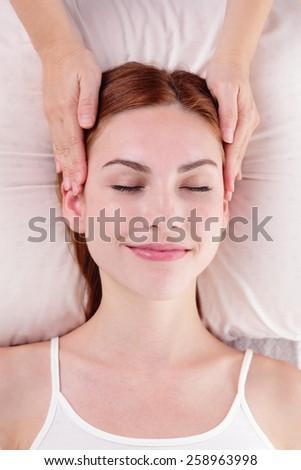 Beautiful young woman enjoy face massage at spa, caucasian beauty - stock photo