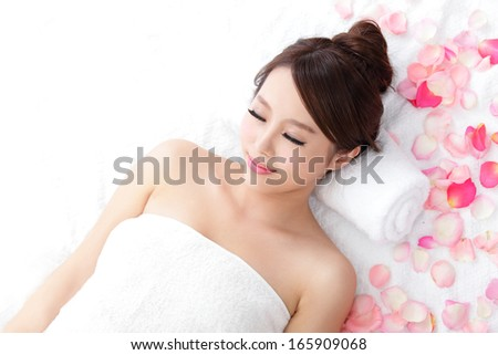 Beautiful young woman enjoy massage at spa with roses, she is very relaxed, asian beauty