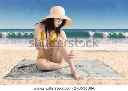 Beautiful young woman enjoy summer holiday at beach and using sunscreen on her leg skin - stock photo