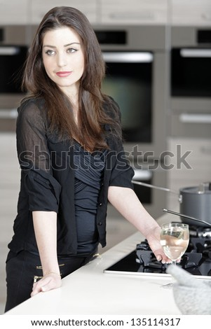 Beautiful young woman enjoying a glass of wine in her kitchen.