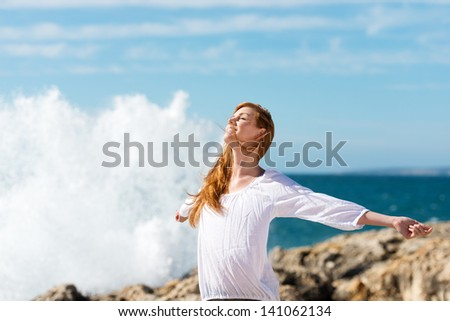 Beautiful young woman enjoying a healthy lifestyle at the sea standing with her arms outspread and head tilted to the sun against the spray of breaking waves - stock photo