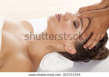 beautiful young woman enjoying a massage of the forehead - stock photo