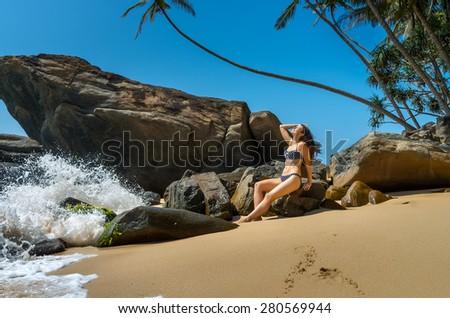 Beautiful young woman enjoying a Sri Lankan beach in Unawatuna - stock photo